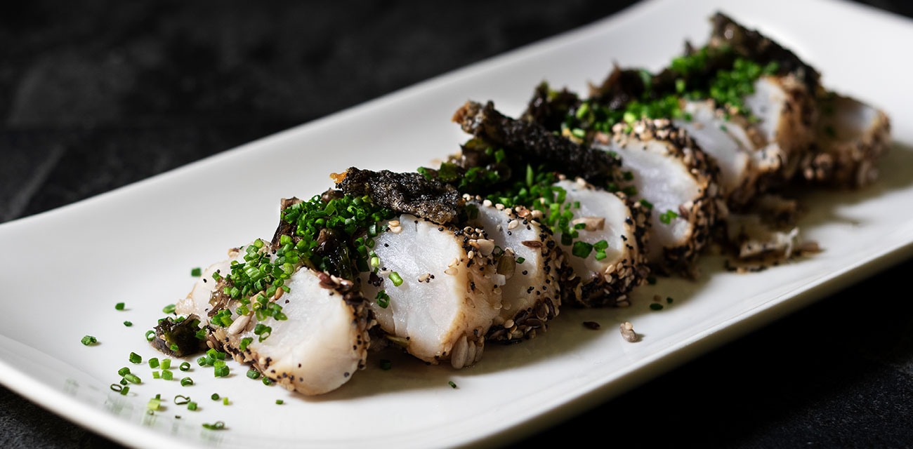 Tataki de lomo de merluza con costra de semillas, combinado de algas y pieles crujientes, sobre cremoso de huevo shichimi togarashi