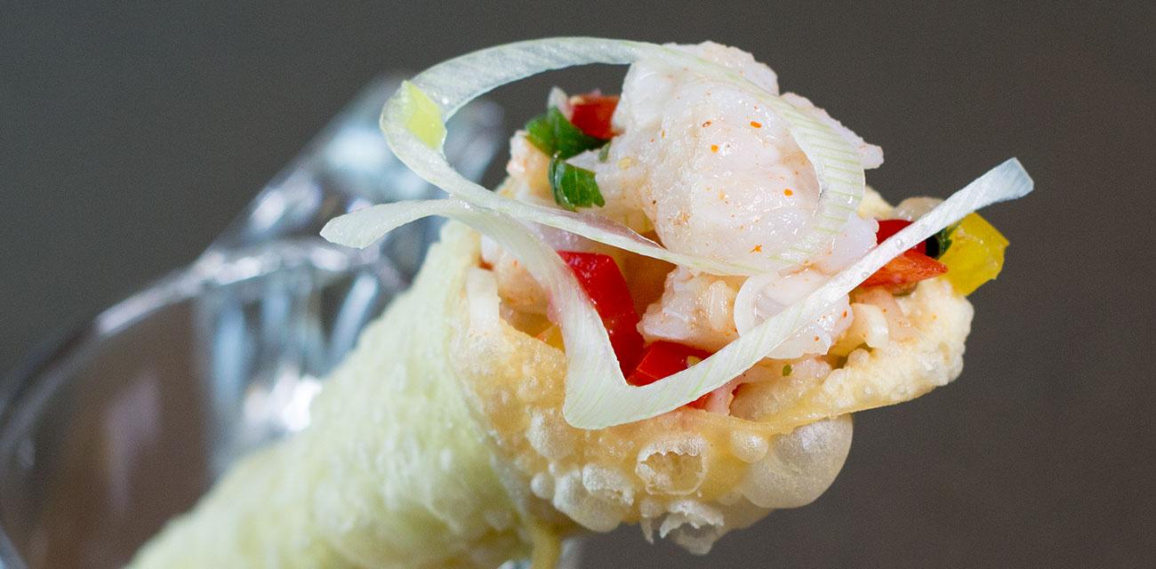 Cono de pestiño salado relleno de cebiche de Merluza Austral Chile sobre leche de tigre