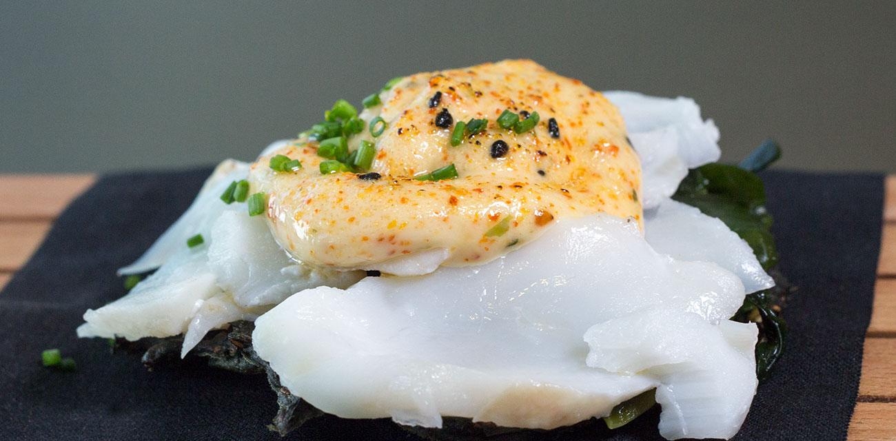 Salsa cremosa Togarashi sobre lasca de Merluza Austral Chile al vapor y galletas de algas