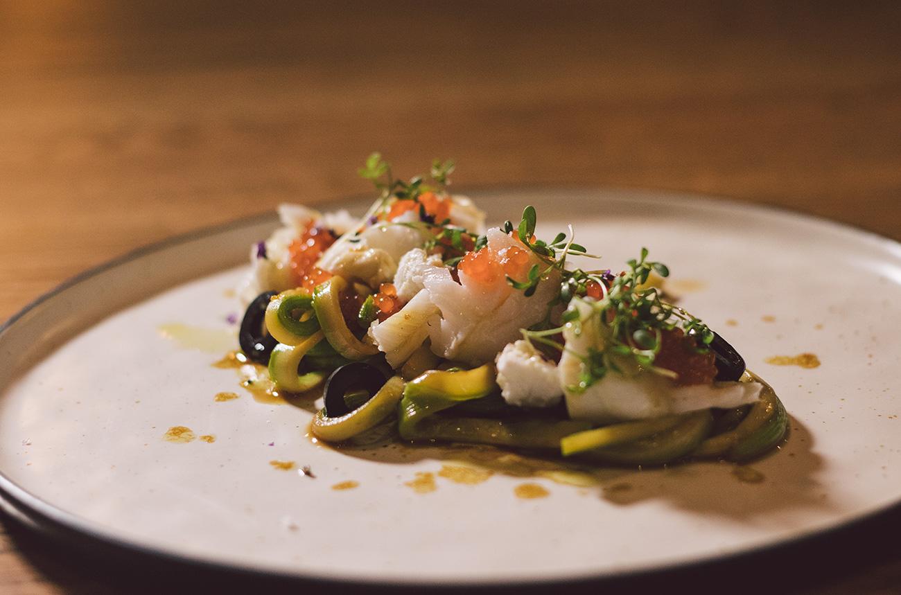 Merluza Austral Chile - Recetas del chef - Merluza confitada en ensalada de calabacín, naranja, queso de cabra y olivas negras